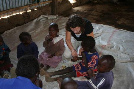 Jennifer helps some children make bracelets