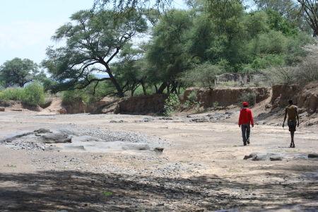 Two Pokot men walk down a dry riverbed